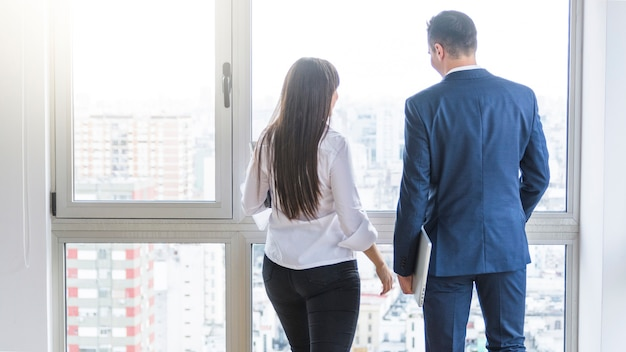 Achtermening van zakenman en onderneemster die uit venster kijken
