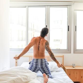 Achtermening van zich het shirtless mens uitrekken op bed