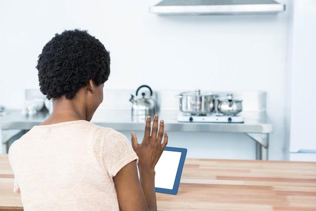 Achtermening van zwangere vrouw die digitale tablet in keuken thuis gebruiken