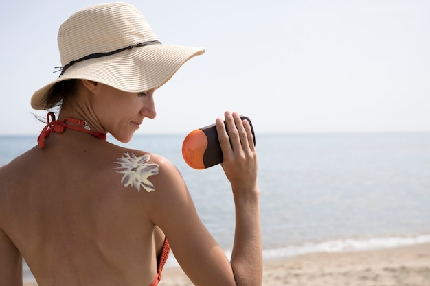 Achtermenings dichte omhooggaande vrouw die zonnescherm op rug toepassen