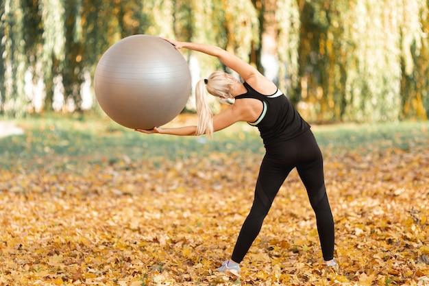 Achtermenings mooie vrouw die een gymnastiekbal gebruiken