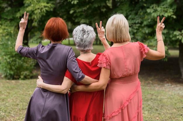 Achtermenings rijpe vrouwen die vredesteken tonen