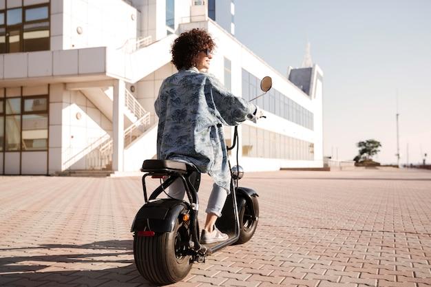 Achtermeningsbeeld van volledige lengte van jonge vrouwenritten op motor