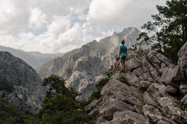 Achtermeningsmeisje die zich op de rots op het mooie landschap bevinden