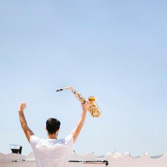 Achtermeningsmens die saxofoon steunen