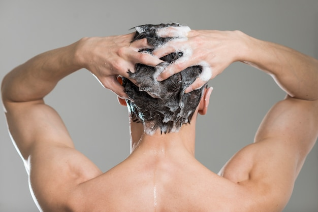 Achtermeningsmens die zijn haar wast