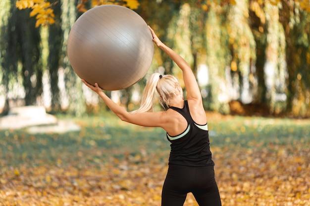 Achtermeningsvrouw die een gymnastiekbal gebruiken