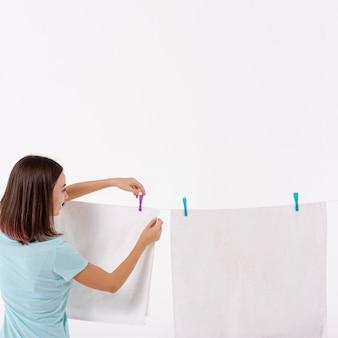 Achtermeningsvrouw die handdoeken op drooglijn schikken