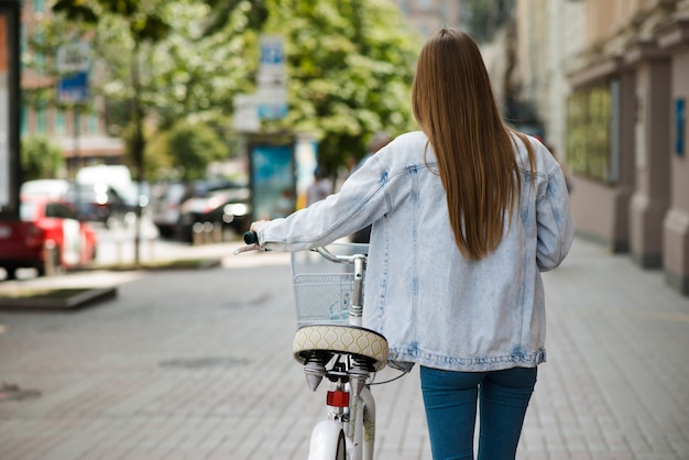 Achtermeningsvrouw die naast fiets loopt