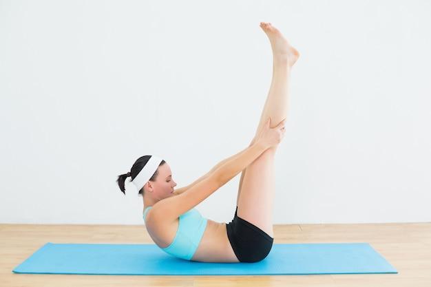 Achterom liggen en vrouw die yoga in geschiktheidsstudio doen
