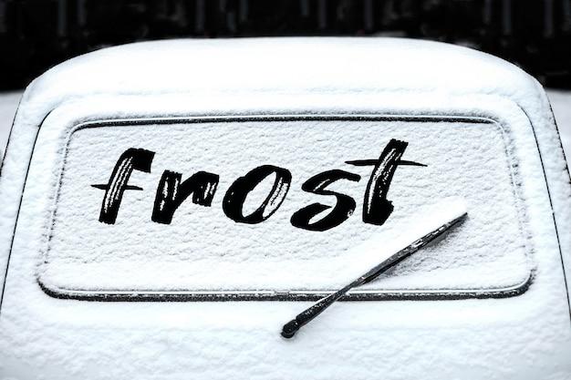 Achterruit autoruit met wisser in de sneeuw