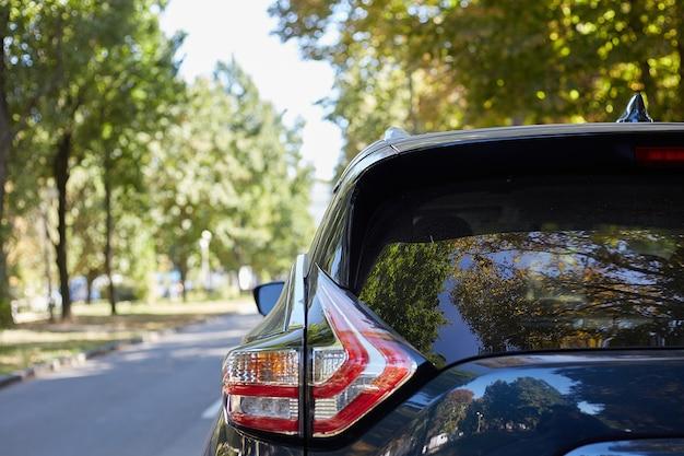 Achterruit van blauwe auto geparkeerd op straat in zonnige zomerdag, achteraanzicht. mock-up voor sticker of emblemen