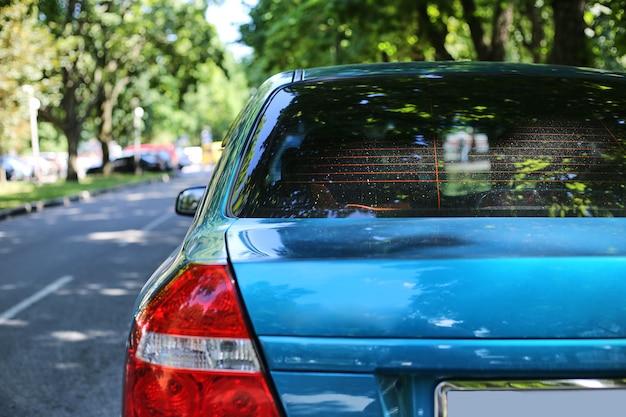 Achterruit van blauwe auto geparkeerd op straat in zonnige zomerdag