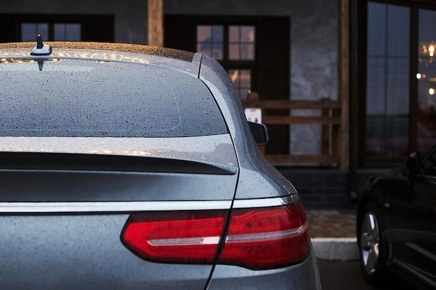 Achterruit van grijze auto geparkeerd op straat in regenachtige herfstdag, achteraanzicht.