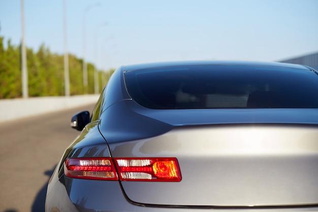 Achterruit van grijze auto geparkeerd op straat in zonnige zomerdag, achteraanzicht. mock-up voor sticker of emblemen