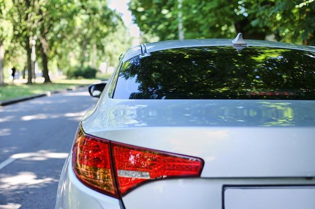 Achterruit van grijze auto geparkeerd op straat in zonnige zomerdag