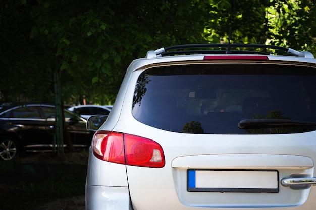 Achterruit van witte auto geparkeerd op straat in zonnige zomerdag, achteraanzicht. mock-up voor sticker of stickers