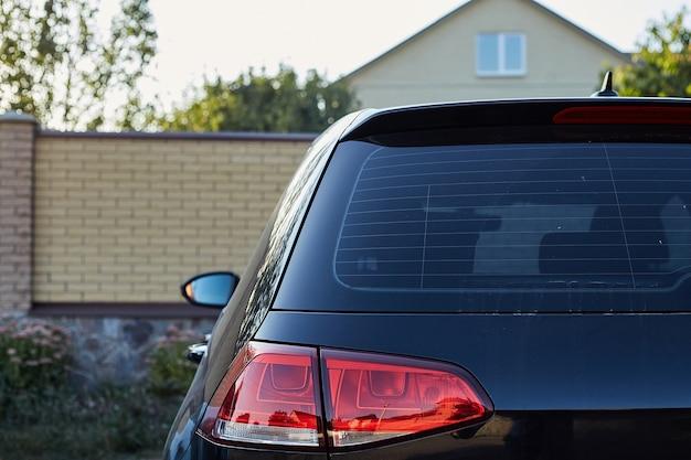 Achterruit van zwarte auto geparkeerd op straat in zonnige zomerdag, achteraanzicht. mock-up voor sticker of emblemen