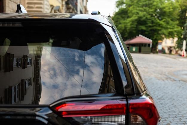 Achterruit van zwarte auto geparkeerd op straat in zonnige zomerdag achteraanzicht mockup voor sticker of emblemen