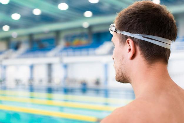Achterschot van geconcentreerde zwemmer