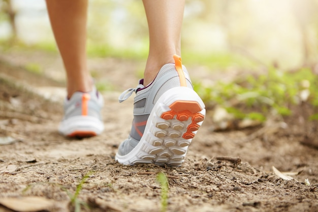 Achterste bijgesneden schot van atletische benen van vrouw jogger roze loopschoenen dragen tijdens het joggen oefening buitenshuis.
