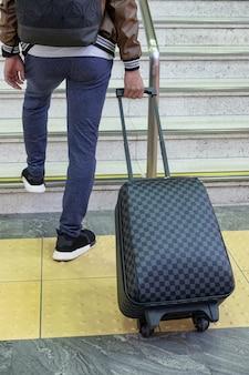 Achterste man reiziger sleept schaakbord bagage op trappen bij metro