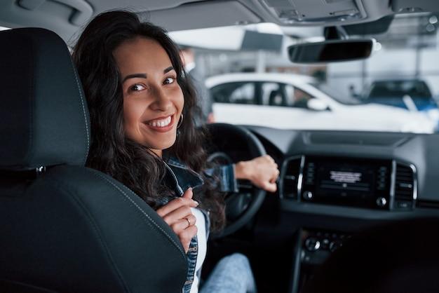 Achteruit gaan. meisje met zwart haar probeert haar gloednieuwe dure auto in de autosalon
