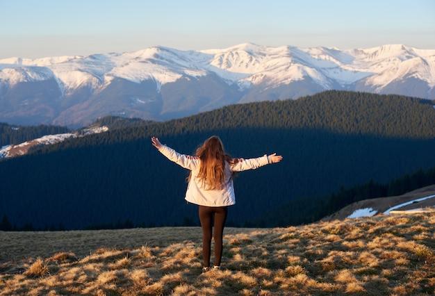 Achteruitkijkschot van een avontuurlijke meisjeswandelaar die zich bovenop de berg met haar uitgespreide wapens bevindt