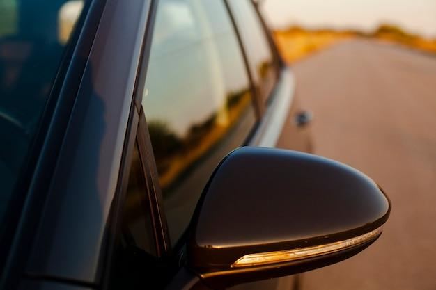 Achteruitkijkspiegel op de achtergrond van de weg