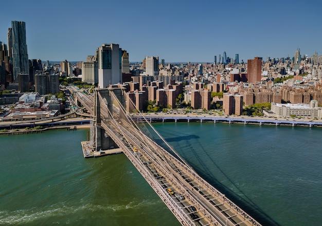 Achterwaarts uitzicht over brooklyn bridge door de east river naar manhattan district vs vliegen