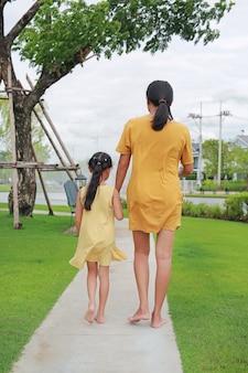 Achterzijde van moeder en dochter hand in hand ontspannen wandelen in de tuin buiten. moeder en kind tijd samen doorbrengen in zomer park