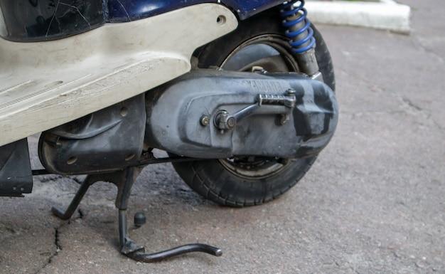Achterzijde wiel met voetsteun op een geparkeerde scooter. close-up van banden van een scooter. achtervering van de scooter. vergrote weergave van het achterwiel van een mini-motorfiets.