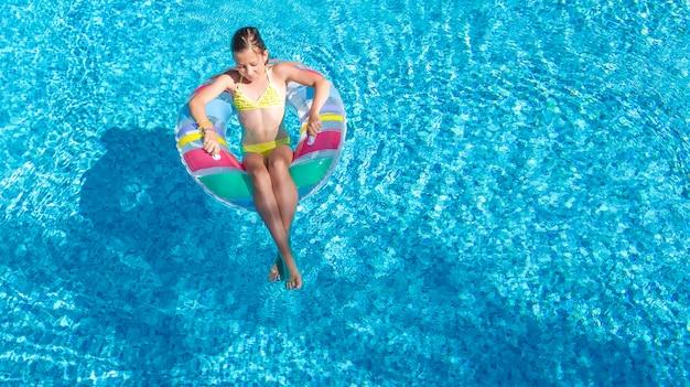 Acrive meisje in zwembad luchtfoto bovenaanzicht van bovenaf, kind zwemt op opblaasbare ring donut, kind heeft plezier in blauw water op familie vakantieoord