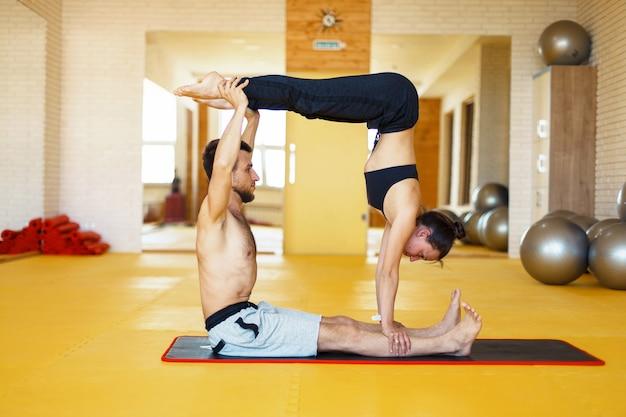 Acro yoga, twee sportieve mensen beoefenen yoga in paar, paar doet rekoefeningen in de sportschool