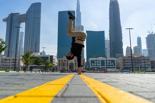 Acrobat houdt de handen in evenwicht met het wazige stadsbeeld van dubai. concept van modern, zakelijk en onbeperkte mogelijkheden.