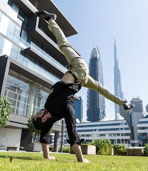 Acrobat houdt de handen in evenwicht met het wazige stadsbeeld van dubai