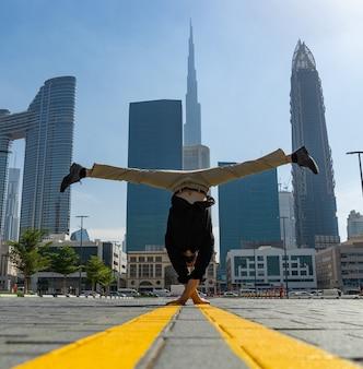 Acrobat houdt een van de handen in evenwicht met het wazige stadsbeeld van dubai. concept van modern, zakelijk en onbeperkte mogelijkheid.
