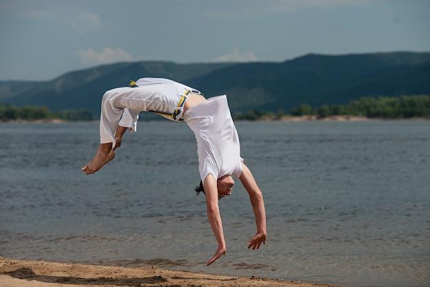 Acrobat voert een acrobatische truc uit, een salto op het strand