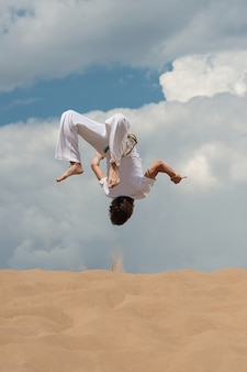 Acrobat voert een acrobatische truc uit, salto op het strand.