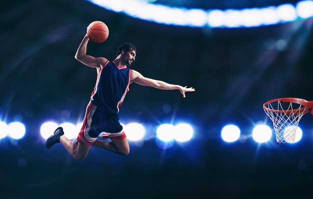 Acrobatische slam dunk van een basketspeler in de basket bij het stadion