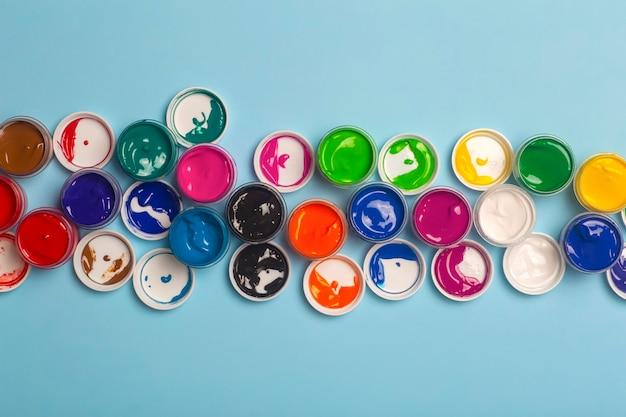 Acrylverf in verschillende kleuren om te tekenen zijn open op tafel. heldere kleurrijke achtergrond van verfblikken