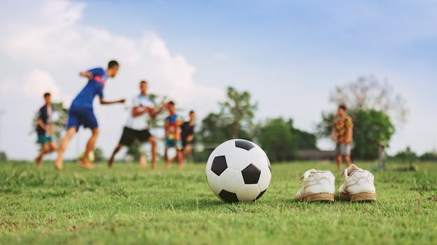 Actie sport buitenshuis van diversiteit aan kinderen die plezier hebben met voetballen voetbal