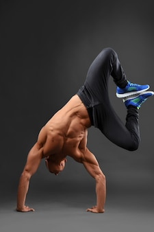 Actief blijven. volledig lengteportret van een shirtless sterke mens die een handstand op grijs doet