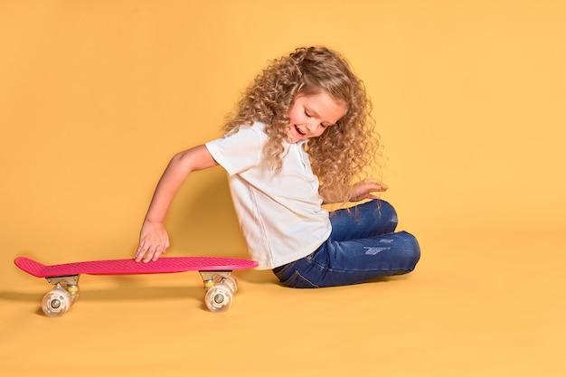 Actief en gelukkig meisje met krullend haar, koptelefoon plezier met cent board