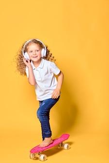 Actief en gelukkig meisje met krullende haarhoofdtelefoons die pret hebben