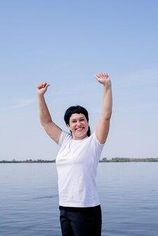 Actief en gelukkig senior vrouw trainen in de buurt van de rivier staan met armen omhoog
