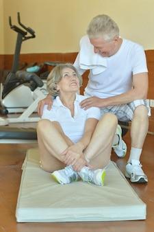 Actief glimlachend hoger paar dat in gymnastiek uitoefent