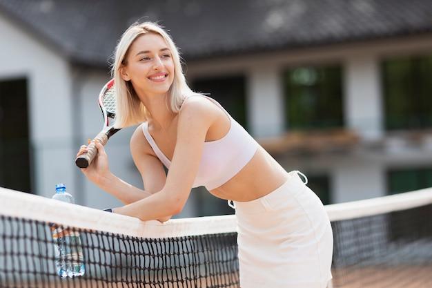 Actief jong meisje dat op het tennisnet rust