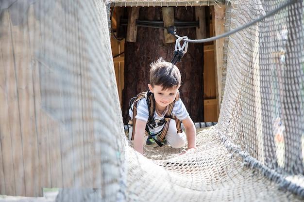 Actief klein kind dat op netto het beklimmen speelt. kinderen spelen en klimmen buitenshuis op zonnige zomerdag.