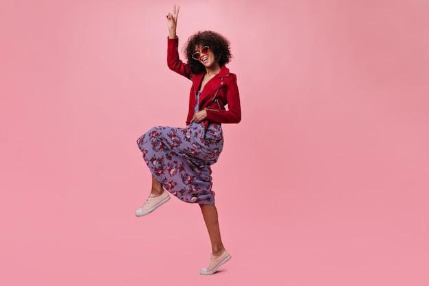 Actief meisje in rood jasje en gebloemde jurk toont vredesteken op roze muur